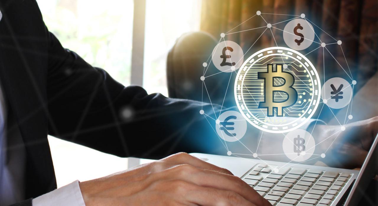 Empresario pagando en bitcoin, usando portátil con pantalla virtual
