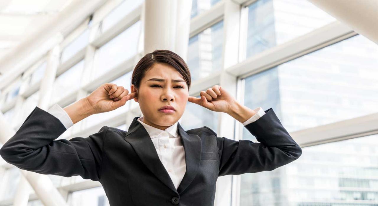Mujer tapándose los oídos por contaminación acústica
