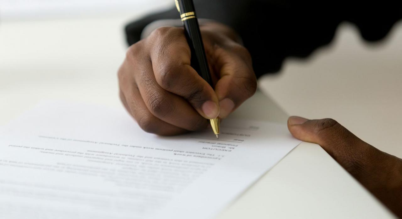 Persona realizando la firma de contrato bancario