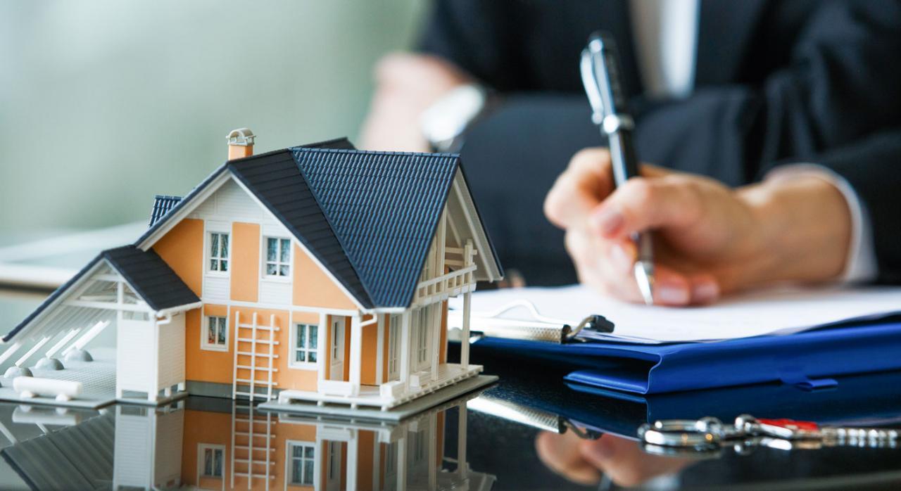Firma de préstamo hipotecario frente a la maqueta de una casa